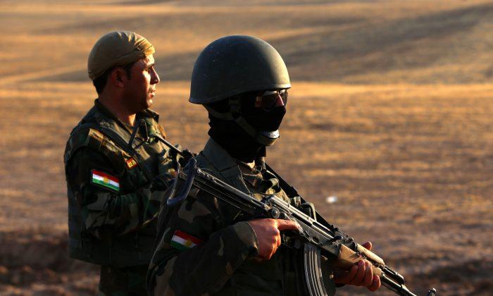 Iraqi Kurdish Peshmerga fighters take position on the front line in Khazer, near the Kurdish checkpoint of Aski kalak near the capital of the autonomous Kurdish region of northern Iraq, on August 14, 2014. (Safin Hamed/AFP/Getty Images)