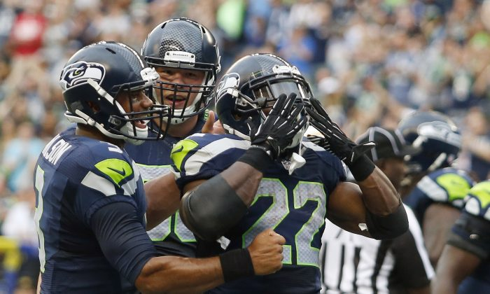 Seattle Seahawks quarterback Russell Wilson, left, and offensive tackle Justin Britt, second from left, celebrate with running back Robert Turbin (22) after Turbin scored a touchdown against the San Diego Chargers in the first half of a preseason NFL football game, Friday, Aug. 15, 2014, in Seattle. (AP Photo/John Froschauer)