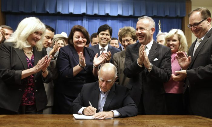 Gov. Jerry Brown receives applause from lawmakers as he signs a measure to place a $7.5 billion water plan on the November ballot on Aug. 13, in Sacramento, Calif. (AP Photo/Rich Pedroncelli)