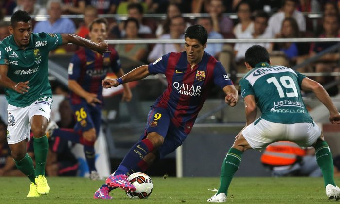 Barcelona's Luis Suarez from Uruguay fights for the ball against Leon's Luis Antonio Delgado, left, and Jonny Magallon, during the Joan Gamper trophy friendly soccer match between Barcelona and Leon at the Camp Nou stadium in Barcelona, Spain, Monday, Aug. 18, 2014. (AP Photo/Emilio Morenatti)