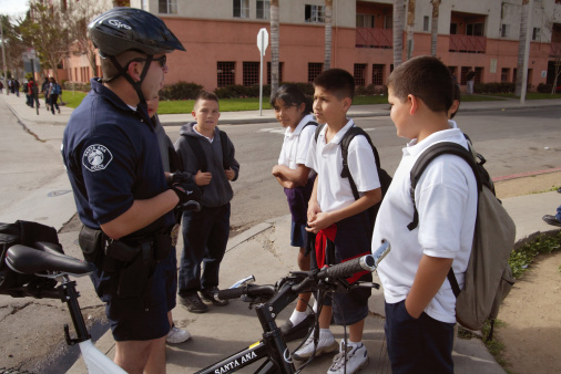 Policeman talking to school kids. (Getty Images)
