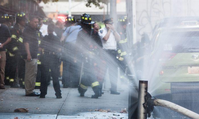 Firefighters outside the scene of contained 4-alarm fire in Upper Manhattan, New York on Aug. 18, 2014. (Petr Svab/Epoch Times)