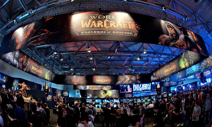 Visitors try out the massively multiplayer online role-playing game 'World Of Warcraft' at the Blizzard Entertainment stand at the 2014 Gamescom gaming trade fair on August 14, 2014 in Cologne, Germany. Gamescom is the world's largest gaming convention and this year includes over 600 exhibitors. (Photo by Sascha Steinbach/Getty Images)