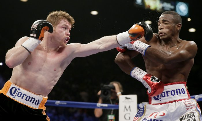 Canelo Alvarez, of Mexico, left, swings at Erislandy Lara, of Cuba during their super welterweight  fight, Saturday, July 12, 2014, in Las Vegas. (AP Photo/John Locher)