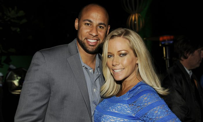 "Hank Baskett, left, a cast member in ""The Hungover Games,"" poses with his wife Kendra Wilkinson at the post-premiere party for the film on Tuesday, Feb. 11, 2014, in Los Angeles. (Photo by Chris Pizzello/Invision/AP)"