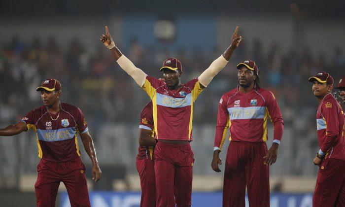 West Indies' captain Darren Sammy, center, celebrates with teammates the dismissal of Sri Lanka's Mahela Jayawardena during their ICC Twenty20 Cricket World Cup semi-final match in Dhaka, Bangladesh, Thursday, April 3, 2014. (AP Photo/Aijaz Rahi)