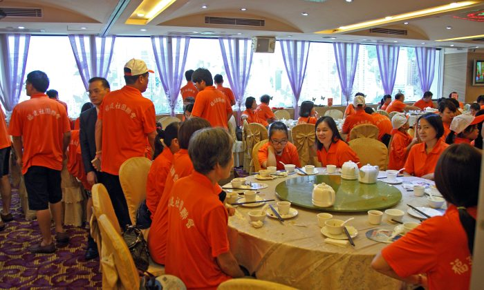 """Protesters in T-shirts with """"Hong Kong Federation of Fujian Associations"""" printed on the back enjoy a restaurant meal as a bribe for joining the recent anti-democracy march in Hong Kong. Pro-CCP groups booked an entire Cantonese restaurant to give feasts to participants. (Epoch Times)"""