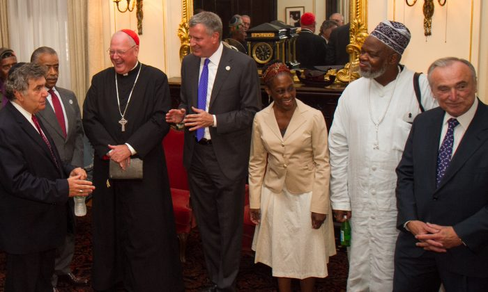 NYC Mayor Bill de Blasio (C) along with his wife (3rd R) meets with Timothy Cardinal Dolan, (3rd L) Rev. Al Sharpton, (2nd L) and commissioner William Bratton, (R) and other clergy members, for an interfaith roundtable meeting in Manhattan, New York on Wednesday, Aug. 20, 2014. (Benjamin Chasteen/Epoch Times)