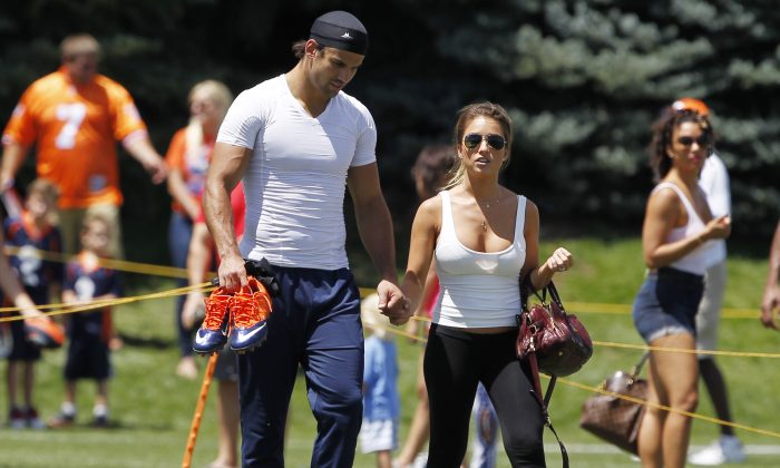 Denver Broncos wide receivr Eric Decker, left, walks off the practice field with his wife, country singer Jessie James, after a session at NFL football training camp in Englewood, Colo., on Friday, Aug. 2, 2013. (AP Photo/David Zalubowski)