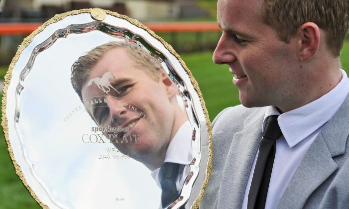 Jockey Tommy Berry poses with The Cox Plate trophy at Moonee Valley Racecourse in Melbourne, Australia, on Aug. 5, 2014. (Vince Caligiuri/Getty Images)