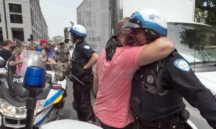 A police officer is hugged by a fellow public sector worker as they protest against proposed pension changes in front of Montreal's city hall on June 17, 2014. Demonstrators' raucous protest at city hall on Aug. 20—and the inaction of Montréal police—has drawn condemnation from Premier Philippe Couillard. (The Canadian Press/Ryan Remiorz)