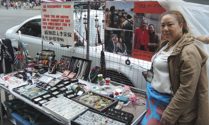 Chun Yin stands by her husband's vendor stall in Chinatown, Manhattan, New York on July 4, 2014. Yin says she is grateful for all the assistance local officials have given in allowing her a temporary license transfer so she can provide for her family. (Epoch Times)