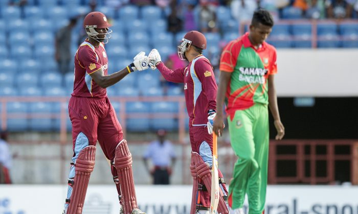 West Indies batsmen Jason Holder (L) celebrates with teammate Suni Narine (C) after scoring the winning run during a One Day International between the West Indies and Bangladesh at Grenada National Cricket Stadium in St. George's, Grenada, August 20, 2014. West Indies defeated Bangladesh 219/9 to 217/9. (Jim Watson/AFP/Getty Images)
