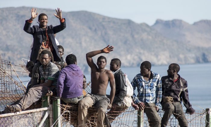 A group of people climbing the fence that separates the borders of Morocco and the Spanish territory of Melilla in an attempt to migrate to Spain, on April 3, 2014. (Blasco Avellaneda/AFP/Getty Images)