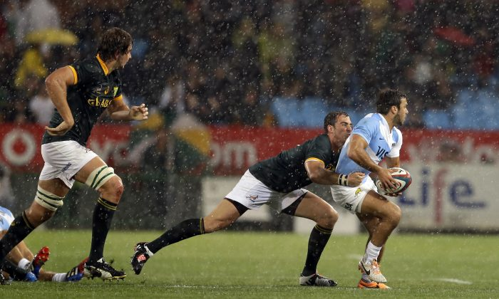 South Africa's Ruan Pienaar, center, tackles Argentina's Martin Landajo, right, during their Rugby Championship match at Loftus Versfeld stadium in Pretoria, South Africa, Saturday, Aug. 16, 2014. (AP Photo/Themba Hadebe)