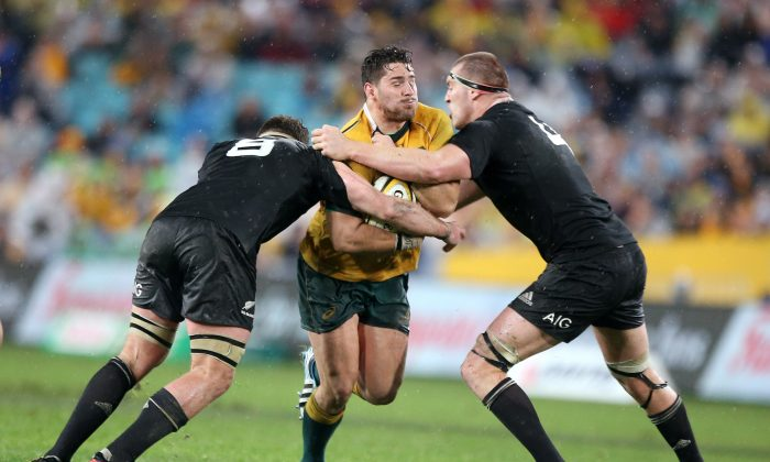 Australia's Nathan Charles, center, charges through the defense of New Zealand's Kieran Read, left, and Brodie Retallic during their Bledisloe Cup rugby union test match in Sydney, Saturday, Aug. 16, 2014. The game is a 12-all draw. (AP Photo/Rick Rycroft)