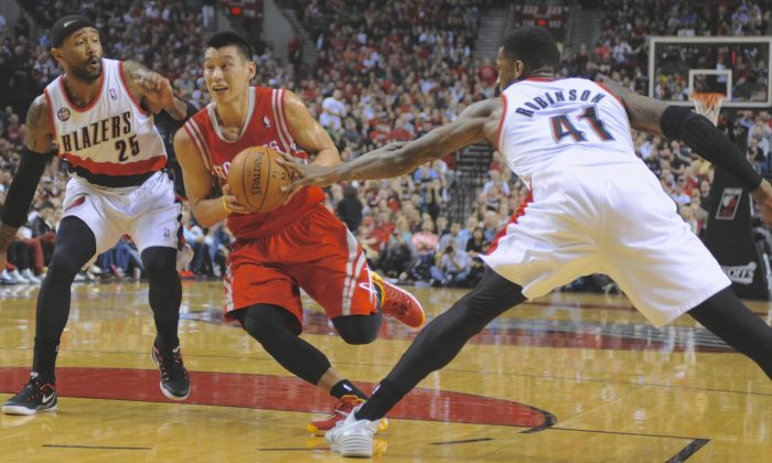 Jeremy Lin (7) drives against Portland Trail Blazers' Thomas Robinson (41) and Mo Williams (25) during the first half of game six of an NBA basketball first-round playoff series game in Portland, Ore., Friday May 2, 2014. (AP Photo/Greg Wahl-Stephens)