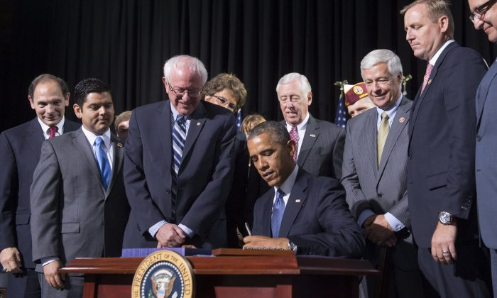 President Barack Obama signs House Resolution 3230, the Veterans Access to Care through Choice, Accountability, and Transparency Act of 2014, at Fort Belvoir in Virginia on Aug. 7, 2014. (Saul Loeb/AFP/Getty Images)