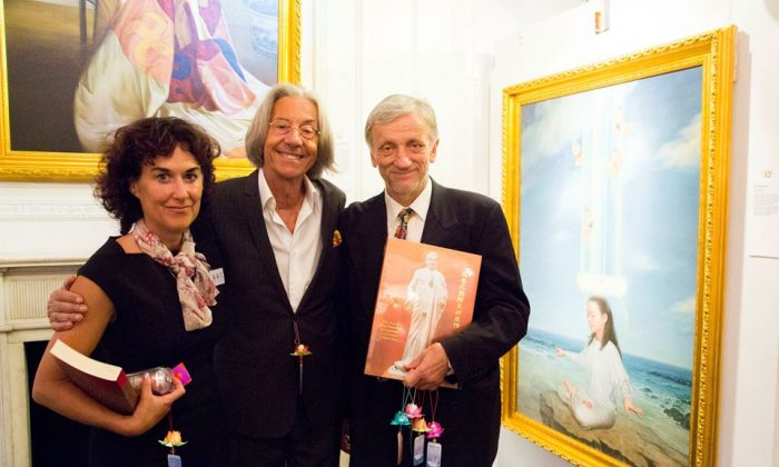 """Organiser Joy Felix (L) and Zek Halu, a long time supporter of the Exhibition, (R) with Elio D'Anna, President and Founder of European School of Economics, standing next to his favourite painting """"In Harmony"""" at The Art of Zhen, Shan, Ren (Truth, Compassion, Tolerance) International Exhibition Private View at Il Bottaccio in London on August 6, 2014. (Simon Gross/The Epoch Times)."""