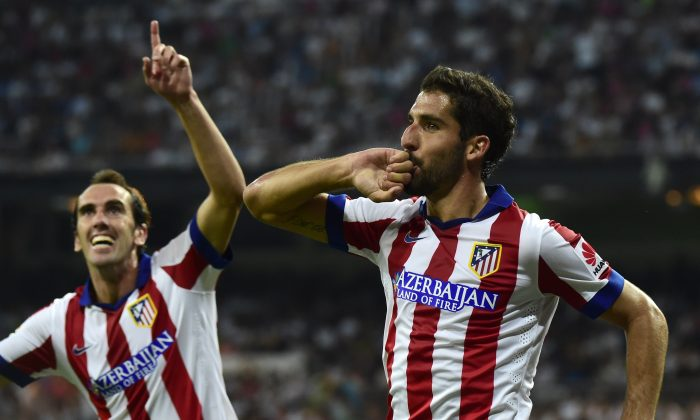 Atletico Madrid's midfielder Raul Garcia (R) celebrates next to Atletico Madrid's Uruguayan defender Diego Godin after scoring during the Spanish Supercup first-leg football match Real Madrid CF vs Club Atletico de Madrid at the Santiago Bernabeu stadium in Madrid on August 19, 2014. (GERARD JULIEN/AFP/Getty Images)