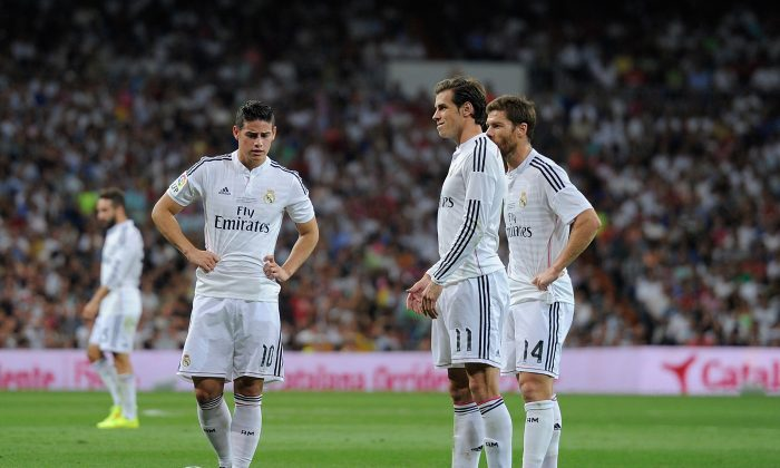Gareth Bale of Real Madrid lines up a free kick beside James Rodriguez (L) and Xabi Alonso during the Supercopa first leg match between Real Madrid and Club Atletico de Madrid at Estadio Santiago Bernabeu on August 19, 2014 in Madrid, Spain. (Photo by Denis Doyle/Getty Images)