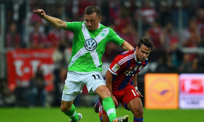 Ivica Olic of VfL Wolfsburg and Juan Bernat of Bayern Muenchen battle for the ball during the Bundesliga match between FC Bayern Muenchen and VfL Wolfsburg at Allianz Arena on August 22, 2014 in Munich, Germany. (Photo by Dennis Grombkowski/Bongarts/Getty Images)