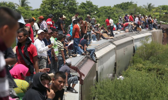 Central American immigrants arrive on top of a freight train to Ixtepec, Mexico, on August 6, 2013. (John Moore/Getty Images)