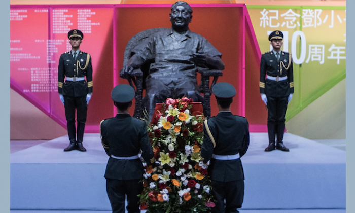 Chinese soldiers place flowers in front of a sculpture of former Chinese leader Deng Xiaoping during the Exhibition of the 110th anniversary of the birth of Deng Xiaoping on Aug. 21, in Hong Kong. This celebration is seen by some analysts as a way of hinting at current leader Xi Jinping's ambitions. (Lam Yik Fei/Getty Images)