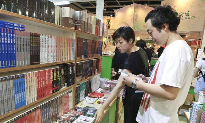 Mainland tourists check books in the section of books that are banned in mainland China. (Yu Gang/Epoch Times)