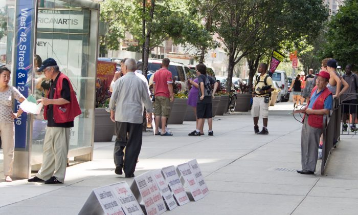Two men in red vests hand out hate materials against the spiritual practice of Falun Gong in front of the Chinese Consulate in New York City on Aug. 5, 2014. (Benjamin Chasteen/Epoch Times)