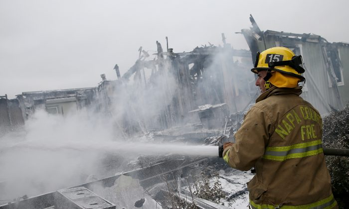 A Napa County firefighter sprays foam on hot spots from a fire at a mobile home park following a reported 6.1 earthquake on August 24, 2014 in Napa, California. (Justin Sullivan/Getty Images)