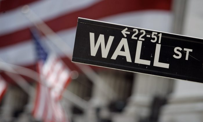 In this May 11, 2007, file photo, a Wall Street sign is mounted near the flag-draped facade of the New York Stock Exchange. (AP Photo/Richard Drew)