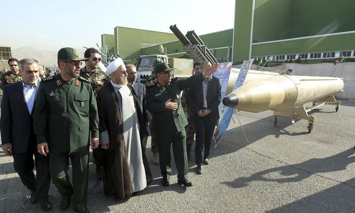 In this photo released by the official website of the office of the Iranian Presidency, Iran's President Hassan Rouhani, center left, visits a defense industry display while listening to explanation of a military official in Tehran, Iran, Sunday, Aug. 24, 2014. (AP Photo/Mohammad Berno, Iranian Presidency Office)