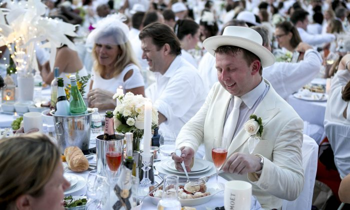 People attend Diner en Blanc (French for Dinner in White) at Nelson A. Rockefeller Park in Battery Park City on August 25, 2014. Approximately 5,000 people attended the pop-up dinner. The event happens once a year in New York and the location remains secret until about an hour before the dinner. (Samira Bouaou/Epoch Times)