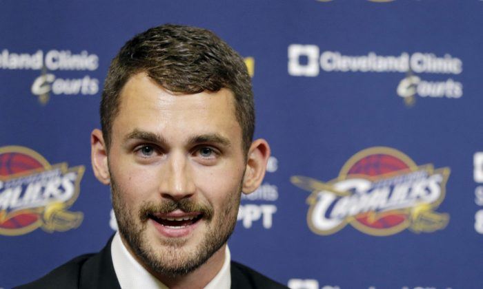 Cleveland Cavaliers' Kevin Love answers questions during his introductory news conference at the NBA basketball team's practice facility in Independence, Ohio  Tuesday, Aug. 26, 2014. (AP Photo/Mark Duncan)