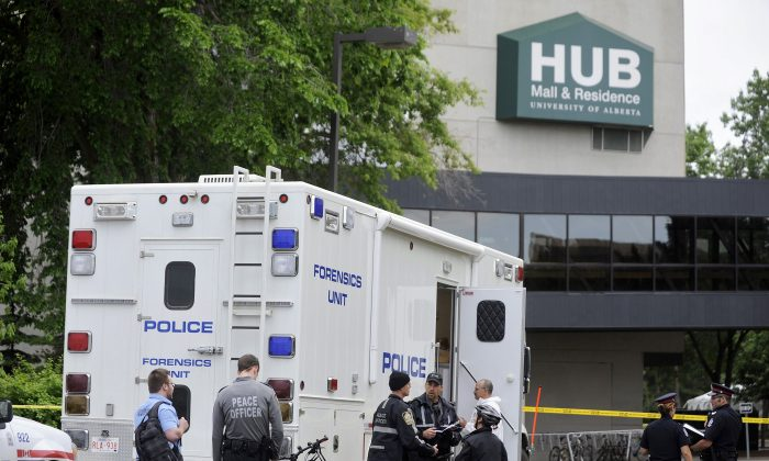 Police investigate the scene of an armoured car robbery at the University of Alberta in Edmonton on June 15, 2012, that left three people dead. Canada's largest union says better safety standards are needed in the armoured vehicle industry. (REUTERS/Dan Riedlhuber)