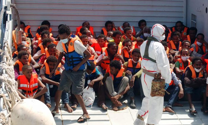 """In this Picture released by the Italian Navy, on Aug. 25, 2014, migrants wait to be boarded on the San Giusto Navy ship, along the Mediterranean sea, off the Sicilian island of Lampedusa, Saturday, Aug. 23, 2014. Italian Interior Minister Angelino Alfano renewed his demand for the European Union to relieve pressure on Italy, which has seen some 100,000 migrants arrive so far this year alone. The country says it spends 9.5 million euros ($13 million) a month to operate the beefed-up air and sea patrols that were launched after more than 360 migrants drowned off the Italian island of Lampedusa last October. """"Italy will make its own decisions"""" if EU partners don't offer assistance, he warned in a tweet. The EU's home affairs commissioner, Cecilia Malmstrom, thanked Italy for its """"huge efforts"""" to save lives and said in a statement she would meet Wednesday with Alfano """"to better define priorities and provide assistance."""" (AP Photo/Italian Navy)"""