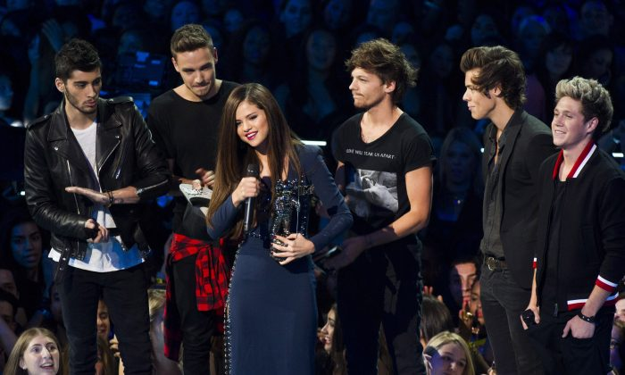 "One Direction presents the award for best pop video for ""Come and Get It"" to Selena Gomez at the MTV Video Music Awards on Sunday, Aug. 25, 2013, at the Barclays Center in the Brooklyn borough of New York. (Charles Sykes/Invision/AP)"