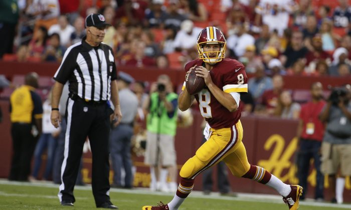 Washington Redskins quarterback Kirk Cousins scrambles with the ball during the first half of an NFL football preseason game against the New England Patriots in Landover, Md., Thursday, Aug. 7, 2014. (AP Photo/Alex Brandon)