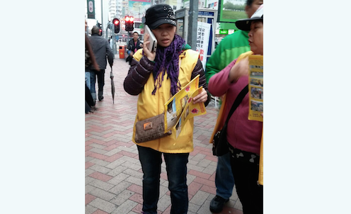Ng Man-ting, a member of the Hong Kong Youth Care Association, dresses in yellow and pretends to be a practitioner of Falun Gong on Argyle Street, Mongkok, in Hong Kong, while handing out propaganda literature against the practice. Ng was recently sent to prison for 12 days. The sentence was suspended for a year. (Epoch Times)