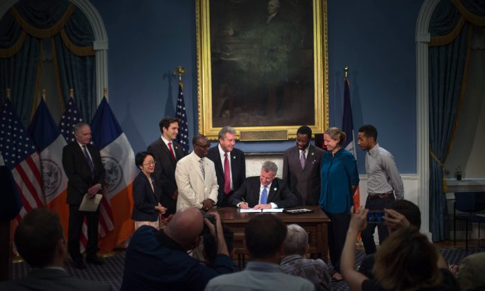 Mayor Bill de Blasio signs a series of bills into law, at the Blue Room in City Hall, New York, on Thursday, Aug. 28, 2014. (New York City Mayor's Office)