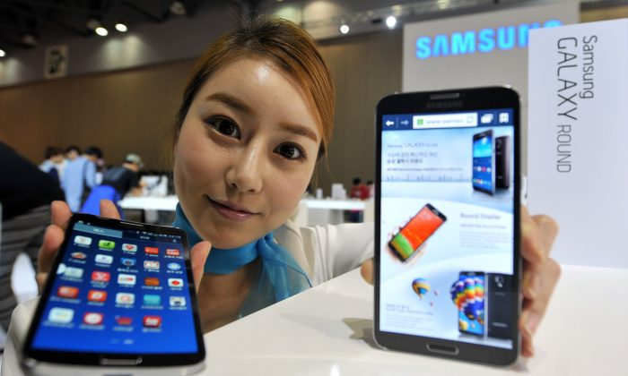 A model holds some electronics by Samsung. South Korean electronic giant Samsung proclaims its ambition to fuel the Internet of Things era. (JUNG YEON-JE/AFP/Getty Images)