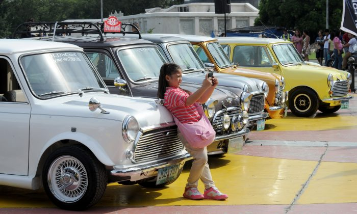 A girl takes a selfie at a Mini Cooper display in Manila on August 10, 2014. The anti-Selfie bill is being heavily criticized. (AFP/Getty Images)