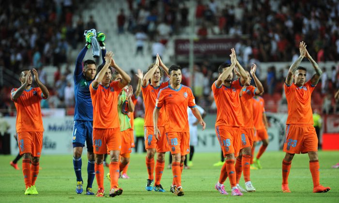 Valencia's players applaud their fans at the end of the Spanish league football match Sevilla FC vs Valencia CF at the Ramon Sanchez Pizjuan stadium in Sevilla on August 23, 2014. The game ended in a draw 1-1. (CRISTINA QUICLER/AFP/Getty Images)