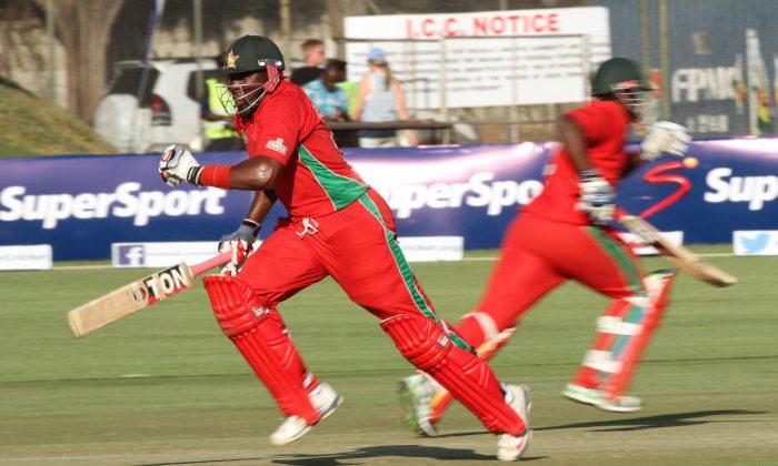 Zimbabwean batsman Hamilton Masakadza, left,  makes a run  on the first  cricket ODI  against  Australia at Harare Sports Club in  Harare Zimbabwe Monday, Aug. 25, 2014. (AP Photo/Tsvangirayi Mukwazhi)