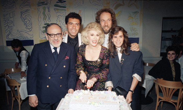 Comic Joan Rivers, center, cut a cake presented by her staff and crew at a party in her honor at the Columbia Bar and Grill in Los Angeles on Sunday, May 18, 1987. Standing at River's side are her husband, Edgar Rosenberg, and her daughter Melissa. In the background are announcer Clint Holmes and musical director Mark Hudson. (AP Photo/Reed Saxon)