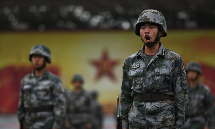 Chinese People's Liberation Army cadets train in Beijing on July 22. The Chinese military is setting new standards for studying Communist doctrine, at the expense of training. (Greg Baker/AFP/Getty Images)