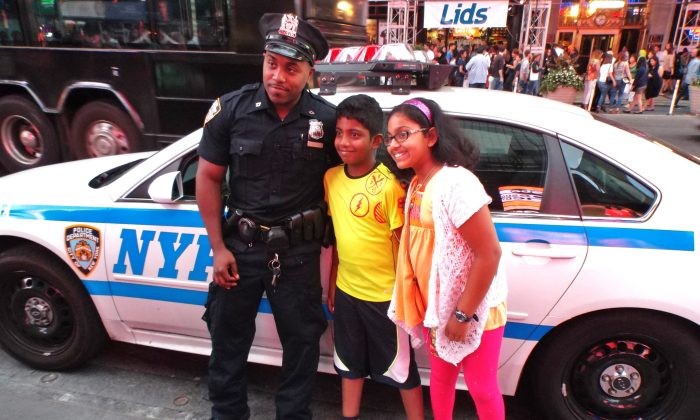 NYPD officer poses with children in Times Square on Aug. 23, 2014. (Vincent J. Bove)