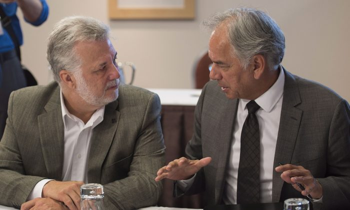 Quebec Premier Philippe Couillard (L) chats with Ghislain Picard of the Assembly of First Nations in Charlottetown Aug. 27, 2014. In the absence of a national inquiry, Canada's premiers and aboriginal leaders are calling on the federal government to participate in a roundtable to address the high number of native women who are missing and murdered. (The Canadian Press/Andrew Vaughan)