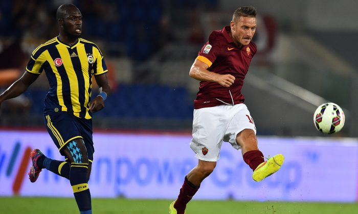 AS Roma midfielder and captain Francesco Totti vies with Fenerbahce forward Moussa Sow (L) during the friendly football match between AS Roma and Fenerbahce, on August 19, 2014 at the Olympic stadium in Rome. (GABRIEL BOUYS/AFP/Getty Images)